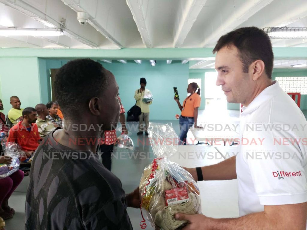 A resident at the Centre for Socially Displaced receives a hamper from Jabbor Kayumov, Digicel CEO. -