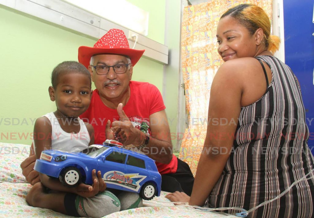 Darwyn Hillaire and his mother Leana Quintero smile after he was presented with a toy car by Health Minister Terrence Deyalsingh at the Wendy Fitzwilliam Children's Hospital on Thursday.  PHOTO BY AYANNA KINSALE - Ayanna Kinsale