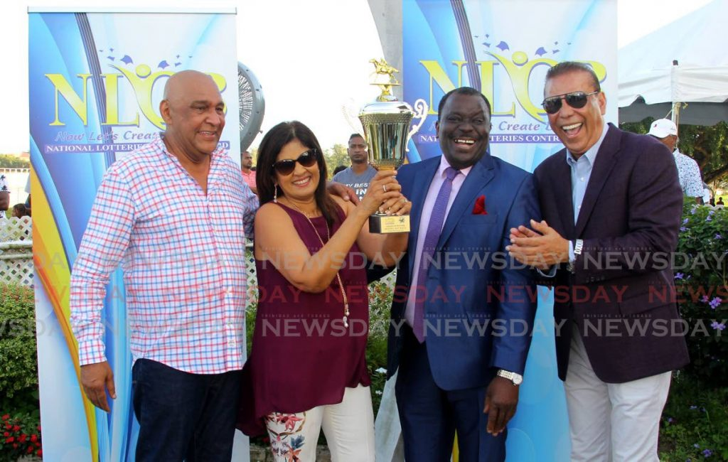 NLCB director Selby Browne (second from right) presents the NLCB Gold Cup trophy to Kamla Maharaj (second from left) yesterday. Also in photo are Kama Maharaj (left) and Arima Race Club's first vice-president Jerry Narace. PHOTO BY ROGER JACOB. - ROGER JACOB