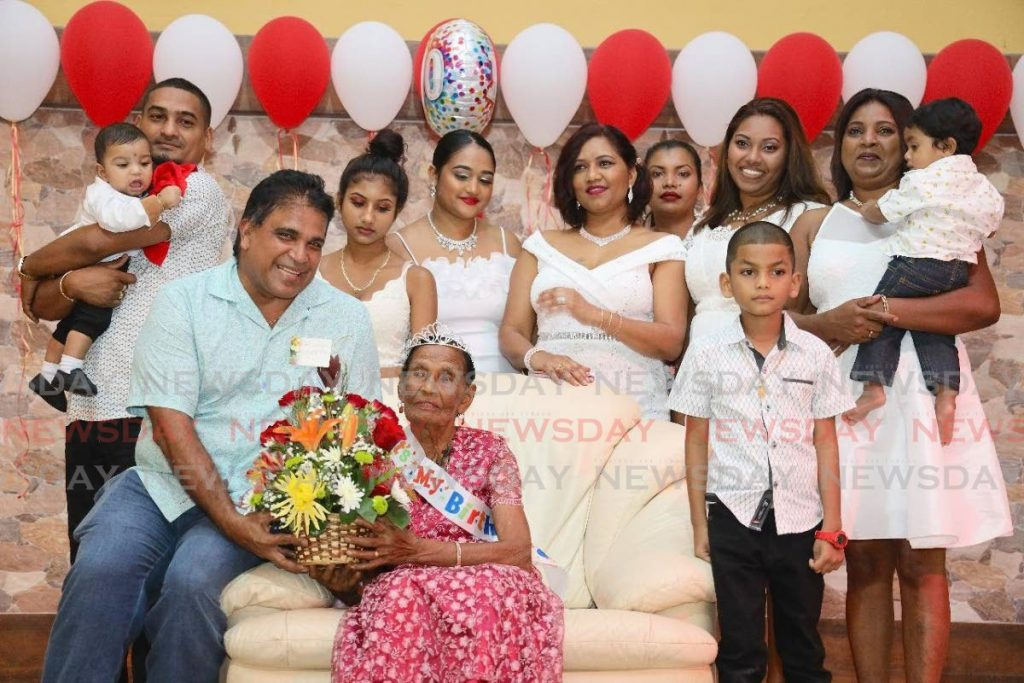 Oropouche East MP Dr Roodal Moonilal presents Mahadeya Arjoon with flowers as she is surrounded by some of her grandchildren. -