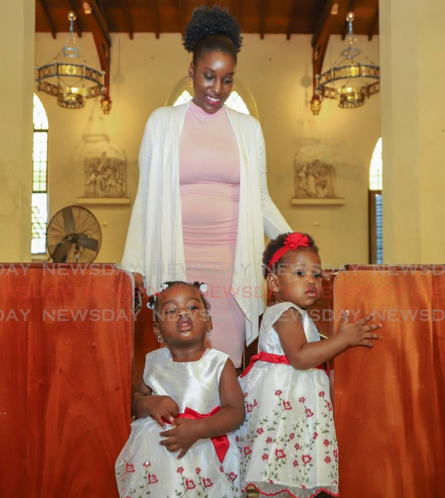 Kailani Melville and Amaya Fletcher with their mother Toya Fletcher during the Holy Innocents mass at the Cathedral of the Immaculate Conception, Port of Spain on Saturday.  - JEFF K MAYERS