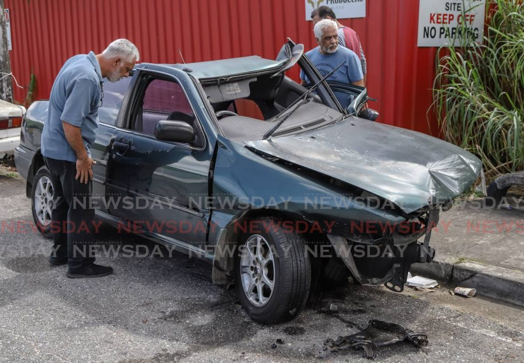 Anthony Persad looks into the car his son was driving when he crashed while driving at St Lucien Road, Diego Martin on Saturday night.  PHOTO BY JEFF K MAYERS - JEFF K MAYERS