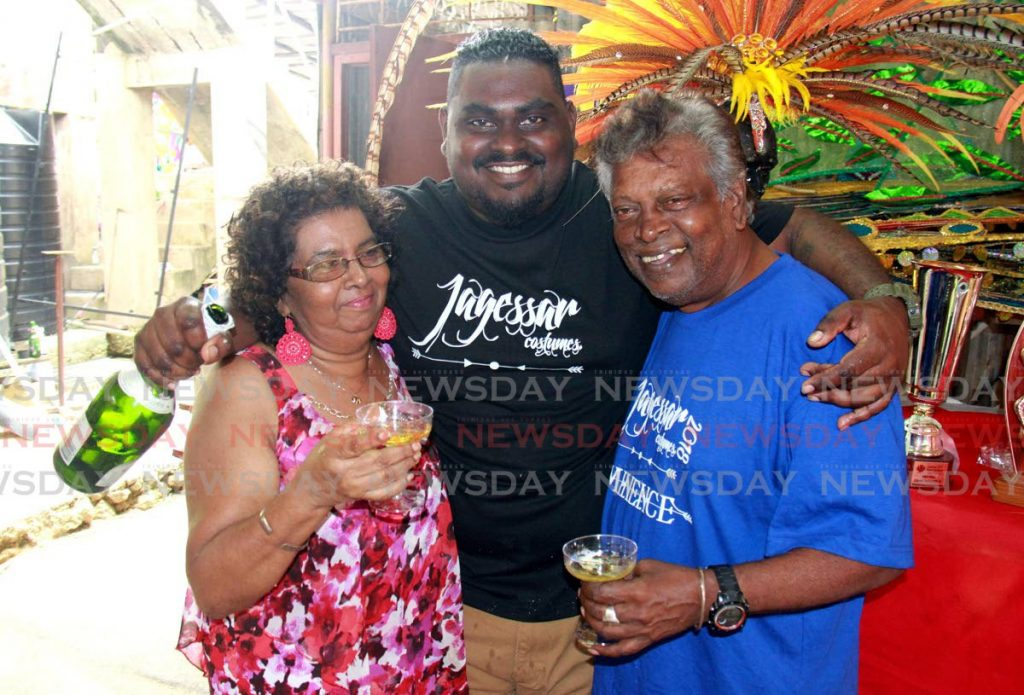 Lionel Jagessar Jr, centre, and his parents Rosemarie and Lionel Jagessar celebrate winning the San Fernando Carnival band of the year title in 2018. The family-led band Jagessar Costumes presents Untamed Territory for 2020 Carnival. FILE PHOTO -