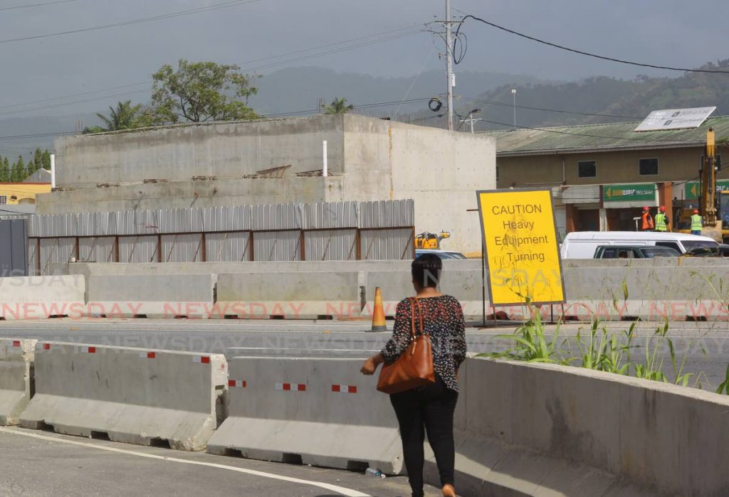 This file photo shows a woman walking near current constrution work at the Curepe Interchange along the Churchill Roosevelt Highway.  -