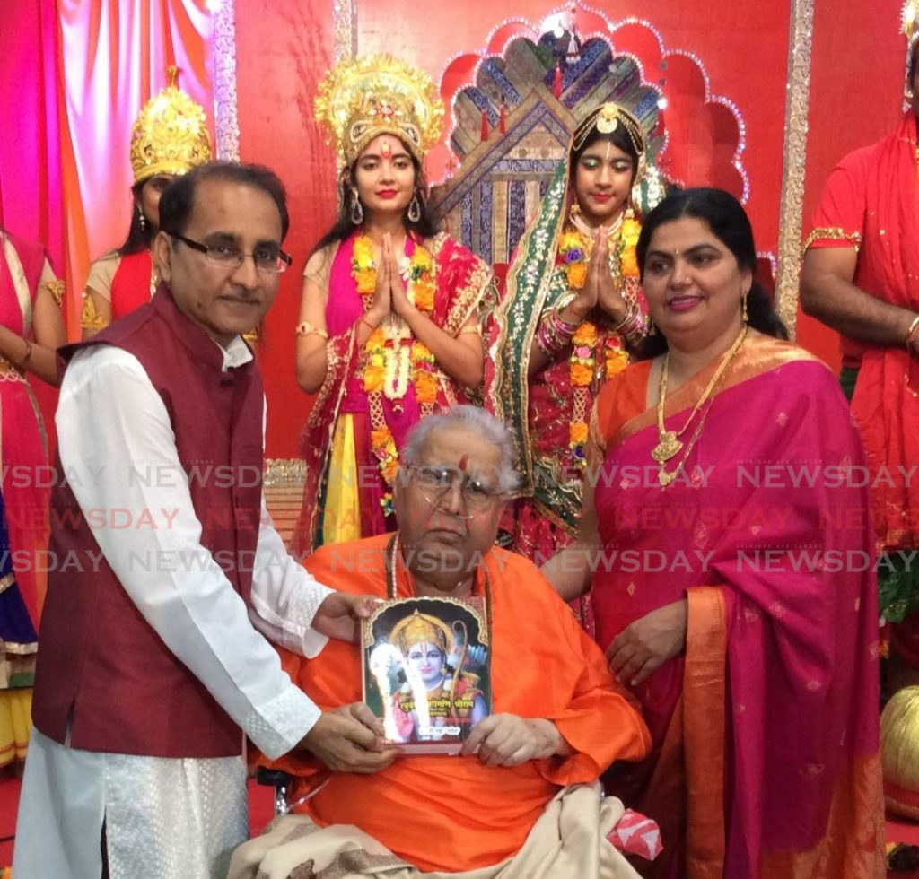 Professor Hari Shanker Adesh, sitting, holds his book Raghuvansh Shiromani Shri Raam, with his son pandit Vivek Adesh, left, and daughter-in-law Shrimati Kadambari Adesh, right. In the background are actors who took part in a drama during the book's launch at Shri Adesh Ashram, Aranjuez.  -