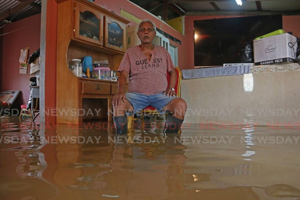 In this December 13, 2019 file photo, Rampersad Ramasar sits in flood waters in his home at Mahadeo Trace, Debe, Trinidad.  - Marvin Hamilton