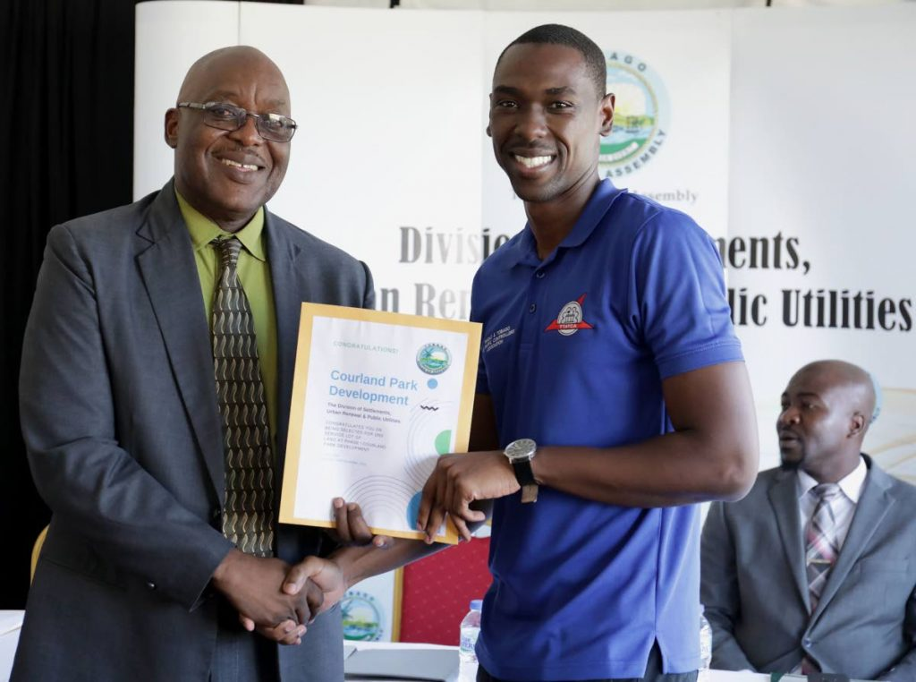 Chief Secretary Kelvin Charles, left, congratulates Randy Agard who was selected as one of the recipients in a land distribution ceremony on Monday at Courland Park Development. PHOTO COURTESY THA - THA