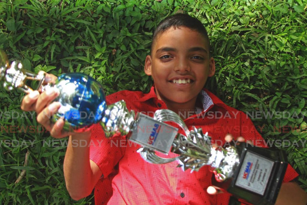 Ivan Christian Maharaj relaxes at Palmiste Park, San Fernando, on December 31, with his trophy from the UCMAS math competition in Cambodia on December 8. - Marvin Hamilton