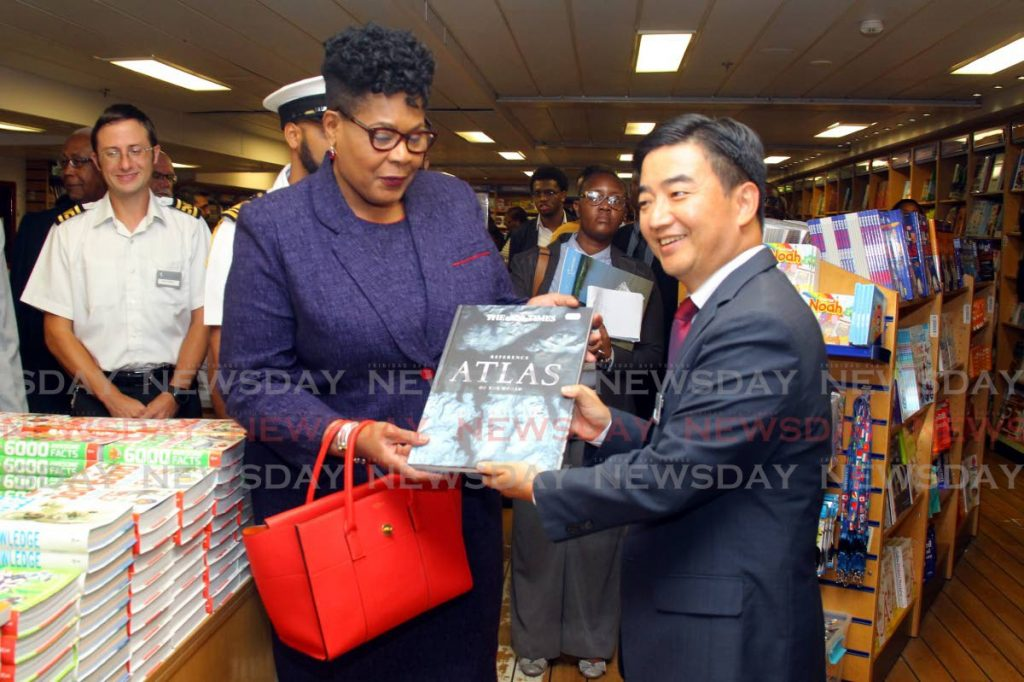 President Paula-Mae Weekes receives a gift from Pil-Hun Park, Director of the MV Logos Hope which docked yesterday at the port in Port of Spain. PHOTO BY ROGER JACOB - ROGER JACOB