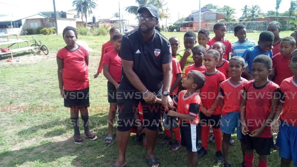 Trini-born, US football coach Anthony Roy, interacts with young football players during his visit to Trinidad in December.  PHOTO COURTESY ANTHONY ROY -