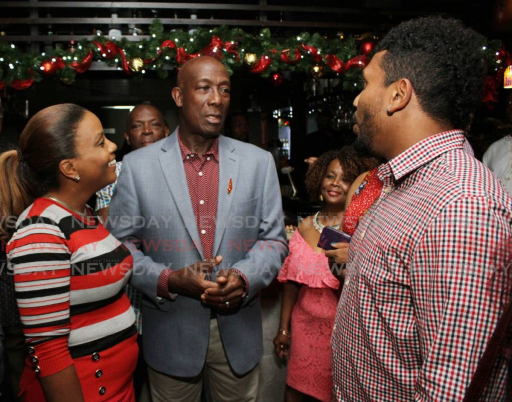 Prime Minister Dr Keith Rowley speaks with Gail Ann Perrotte and her son Randy Mahase at the PNM cocktail reception for members of the media on Wednesday.  PHOTO BY ANGELO M MARCELLE - ANGELO_MARCELLE