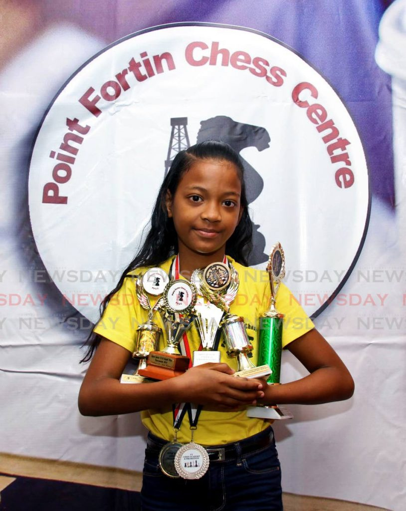 National primary schools chess champion Makayla Joseph cradles her trophies and medals at the Point Fortin Chess Centre, Sissons Infinity Colour Shop, Point Fortin.   - Vashti Singh