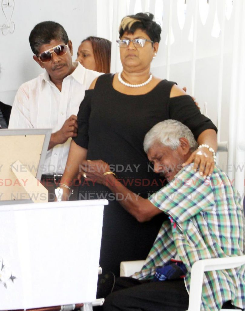Siblings of Randy Chuniesingh console each other during his funeral at Morne Roche Quarry Road, Williamsville on Sunday. - Vashti Singh