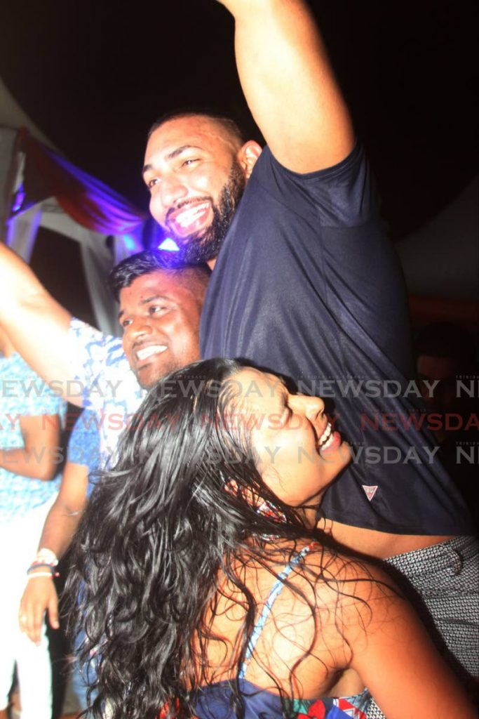 Party goers reverse roles for a 'high lift' at Passage to Asia Restuarant's all-inclusive fete Senses at Jamboree Park, Valsayn on Saturday night. - ANGELO MARCELLE