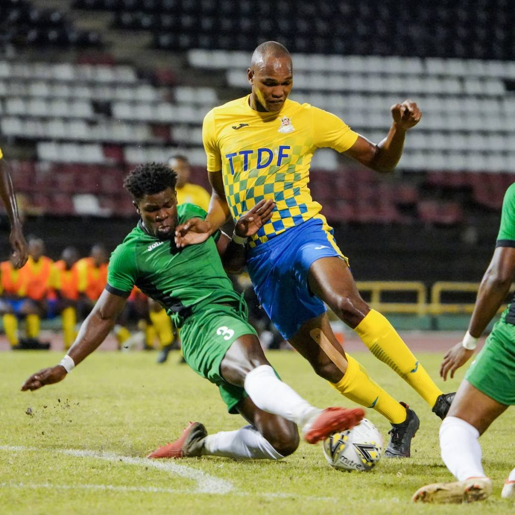Defence Force FC striker Trent Sam (right) gets a heavy skate tackle from W Connection's Isaiah Garcia (No 3) during the TT Pro League match between Defence Force FC and W Connection FC at the Hasely Crawford Stadium, Port of Spain, on Saturday. - Daniel Prentice/CA-images