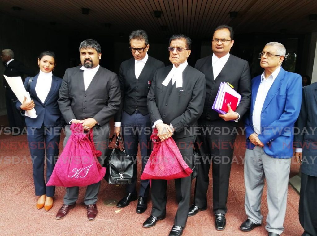 The legal team representing the late Satnarayan Maharaj and his television and radio stations, led by Senior Counsel Ramesh Lawrence Maharaj, outside the Hall of Justice after the ruling. At far right is Vijay Maharaj - son of Satnarayan Maharaj. PHOTO BY KEINO SWAMBER - KEINO SWAMBER