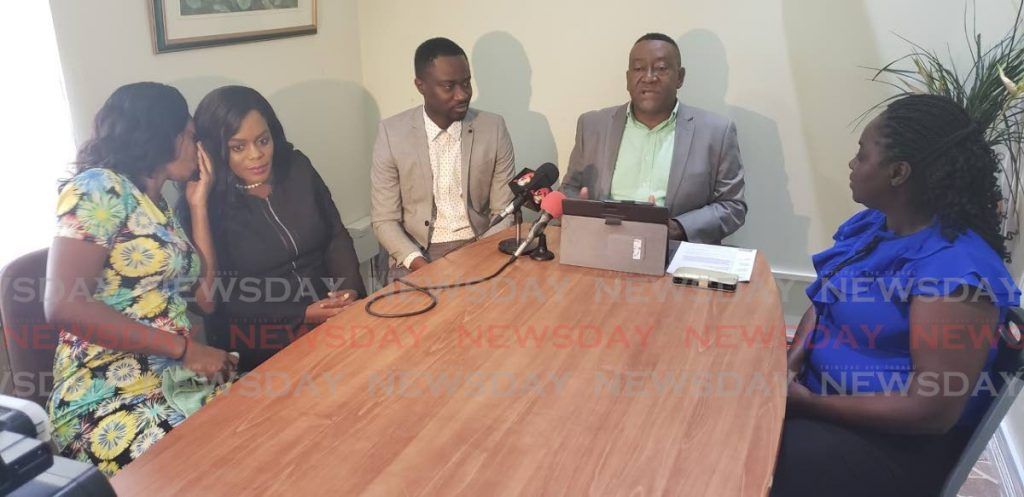 Attorney Martin George, seated at the head of the table, with Farley Augustine, third from left, and other past and current contract teachers at a press conference in Scarborough on Monday. -