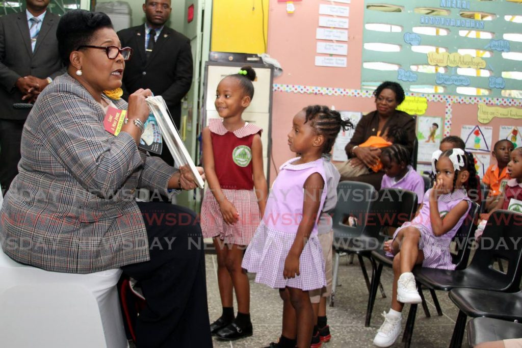 STORYTIME: Children at the All-In-One Development Centre at Beetham Gardens listen to President Paula-Mae Weekes as she reads a story to them on Wednesday.  PHOTO BY ANGELO MARCELLE - Angelo Marcelle