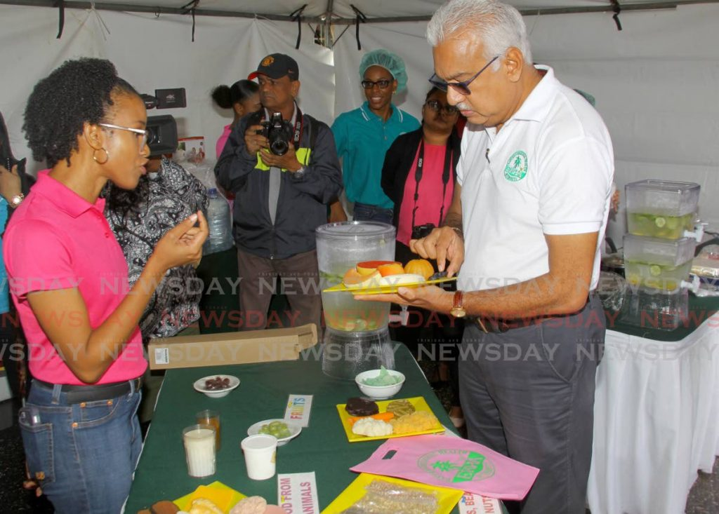 Minister of Health Terrence Deyalsingh holds a proper serving of fruit as nutritionist Dr Candace Simpson-Smith speaks about food portion sizing at the Eastern Regional Health Authority's (ERHA) breast cancer awareness drive at the St Francis of Assisi RC Church, Sangre Grande, Wednesday. - ROGER JACOB