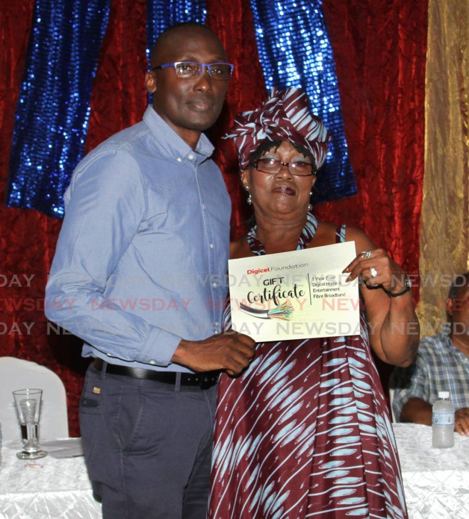 Digicel Foundation's Guy Small presents Morvant Central Community Complex president Pamela Rochard with a Digicel gift certificate for free Internet for one year.  - Angelo Marcelle