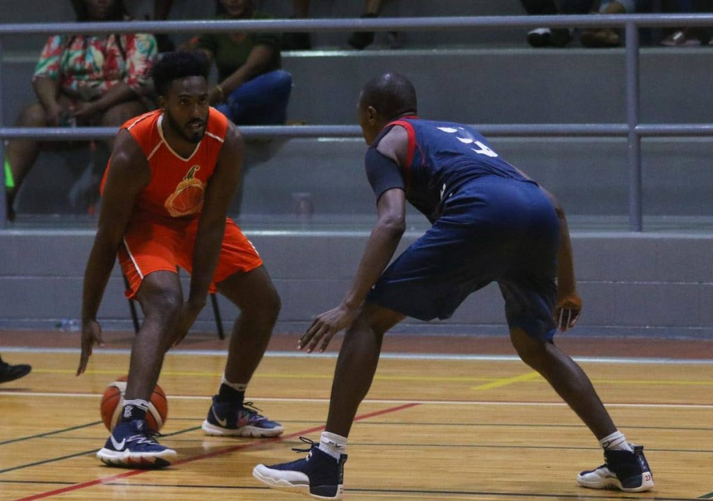 Kemrick Julien dribbles past Defence Force's Kingsley Sandy in a recent National Basketball Federation of TT Invitational tournament game. - Photo courtesy J-M Productions