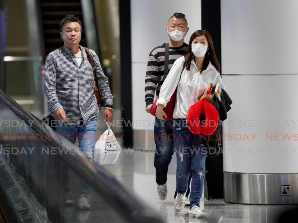 TAKING NO CHANCES: Passengers wear face masks at they arrive at the Kuala Lumpur International Airport in Sepang, Malaysia on Tuesday. (AP) -