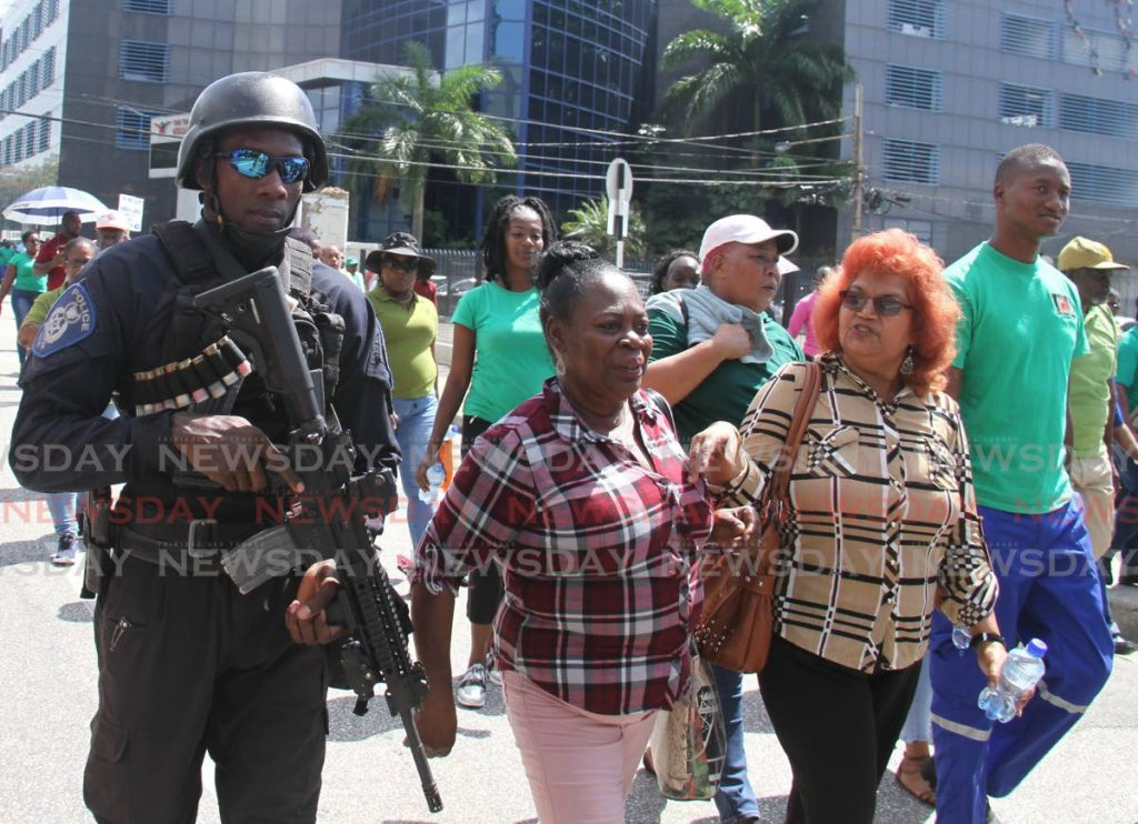 Police stand guard as PTSC and MTS workers protest outside Central Bank in Port of Spain on Tuesday. - Ayanna Kinsale