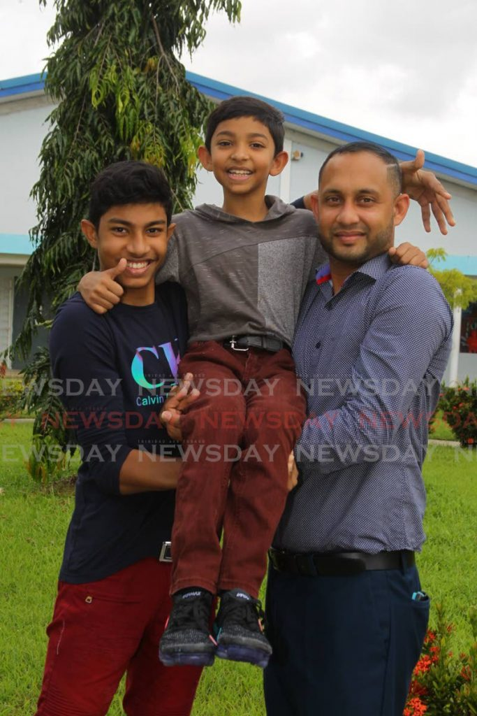 Avindha Singh (centre) is supported by his brother Rohit Singh (left) and father Rishi Singh (right)  - ROGER JACOB