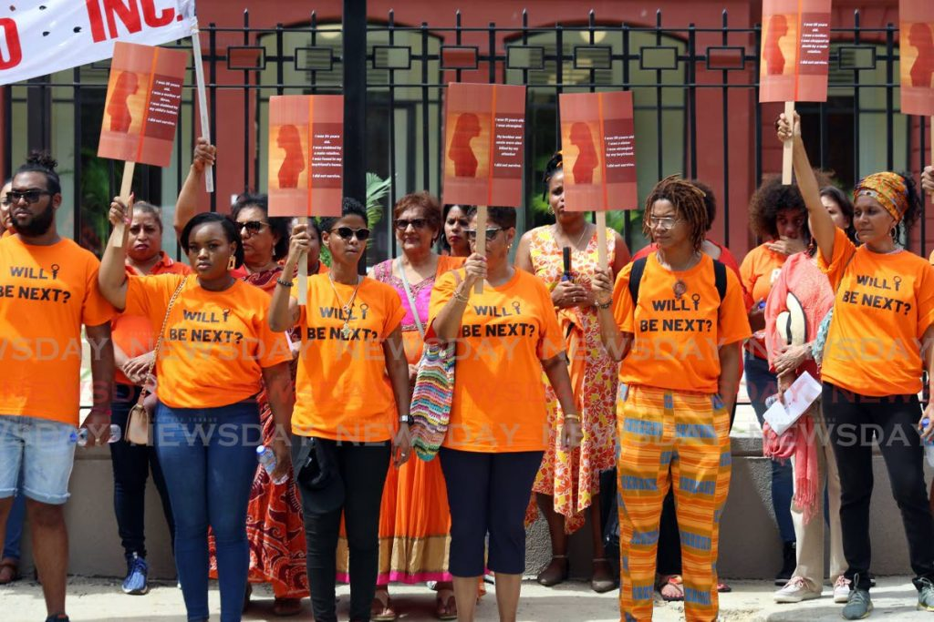 Civil society activists raise signs in support of victims of gender-based violence outside the Red House on Saturday. The police now have a gender-based violence unit to address such crimes. - SUREASH CHOLAI
