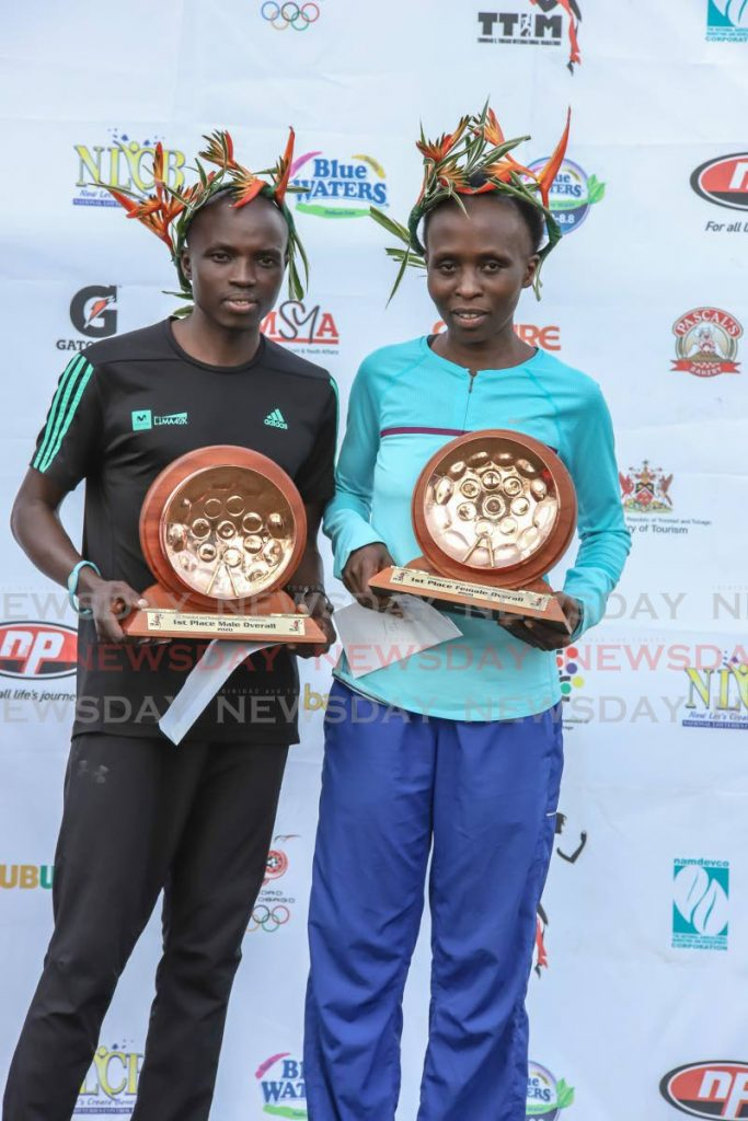 Mexico's Stephen Njoroge (L) and Kenya's Hellen Mugo display their awards after winning the men and women's categories respectively, at the 2020 TT International Marathon, at the Queen's Park Savannah, on Sunday morning. - JEFF K MAYERS