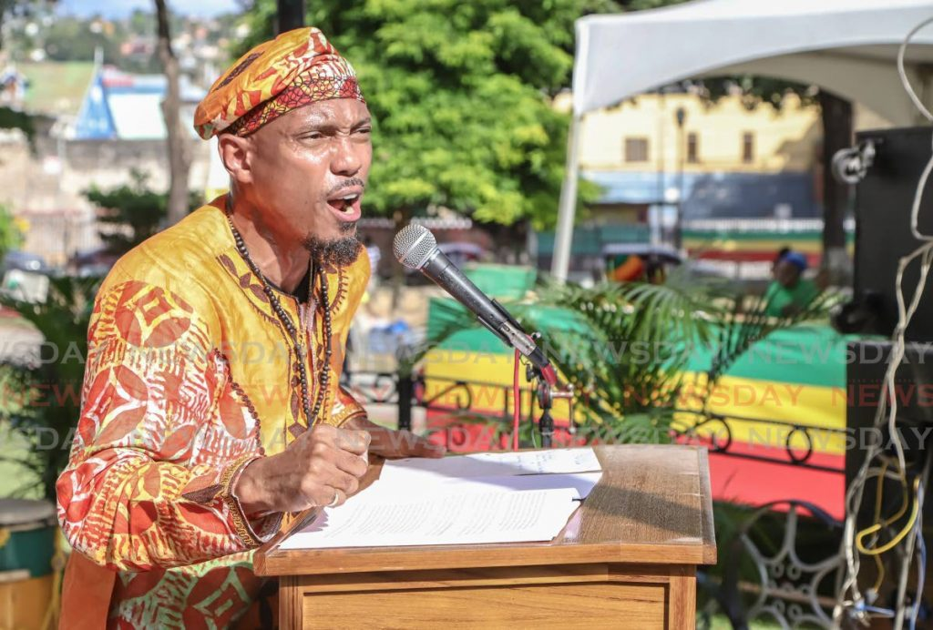 Rev Kwame Kamau speaks at the rally at Woodford Square in Port of Spain on Sunday.   - JEFF K MAYERS