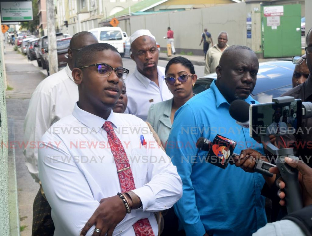 Duaine Hewitt, left, of the Concerned Public Officers speaks to the media concerning issues with Public Servants Association President Watson Duke as Curtis Cuffie, right, looks on outside the PSA's headquarters on Abercromby Street, Port-of-Spain on Monday morning.  - Vidya Thurab