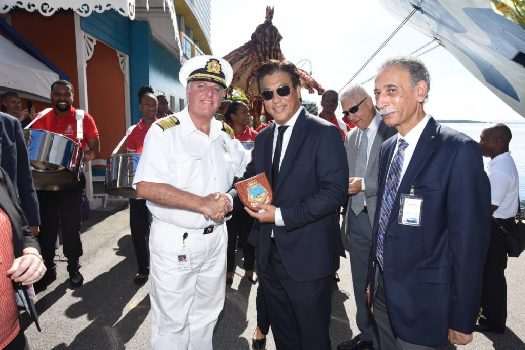Captain Marco Fortezze of the Caribbean Princess cruise liner presents the Chairman of Tourism Trinidad Limited, Howard Chin Lee, with a vessel crest during the November opening of the 2019/2020 cruise season. In the background is the T&T Defence Force Pan Around the Neck Steel Orchestra. PHOTOS BY Tourism TT - Tourism TT