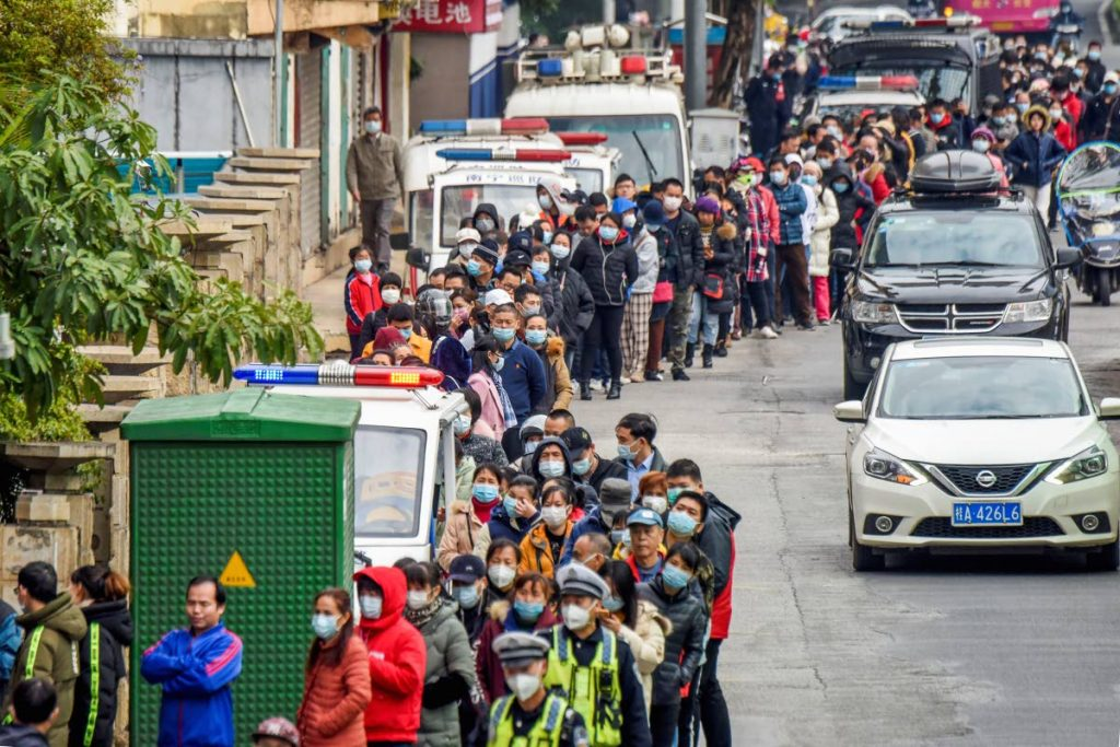 People line up to buy face masks from a medical supply company in Nanning in southern China's Guangxi Zhuang Autonomous Region, Wednesday. Countries began evacuating their citizens Wednesday from the Chinese city hardest-hit by a new virus that has now infected more people in China than were sickened in the country by SARS.  -