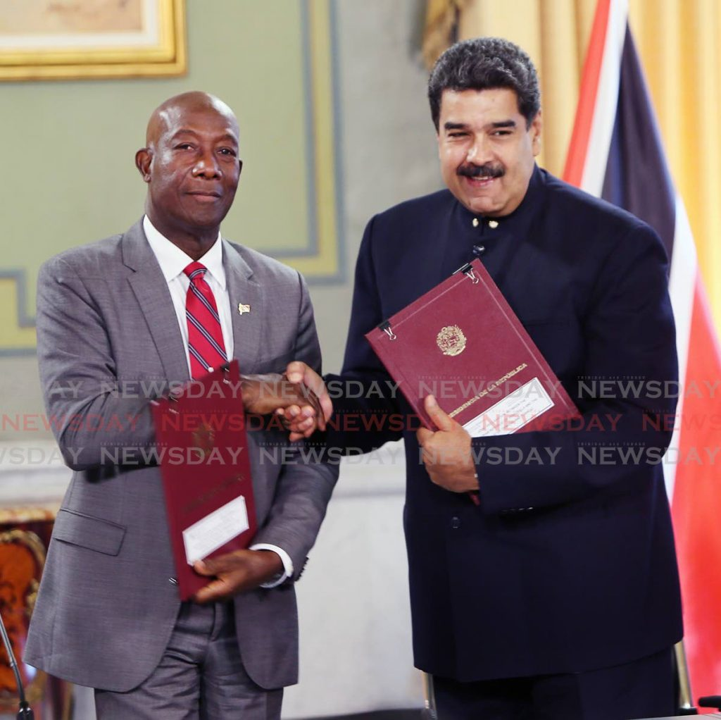 In this August 25, 2018 file photo Prime Minister Dr Keith Rowley, left, and Venezuela's President Nicolas Maduro exchange copies of an agreement on cross-border exploration of the Dragon natural gas field at the Presidential Palace, Caracas, Venezuela. On February 3, 2020, the Prime Minister announced the agreement is now on hold because of US sanctions on Venezuela. -