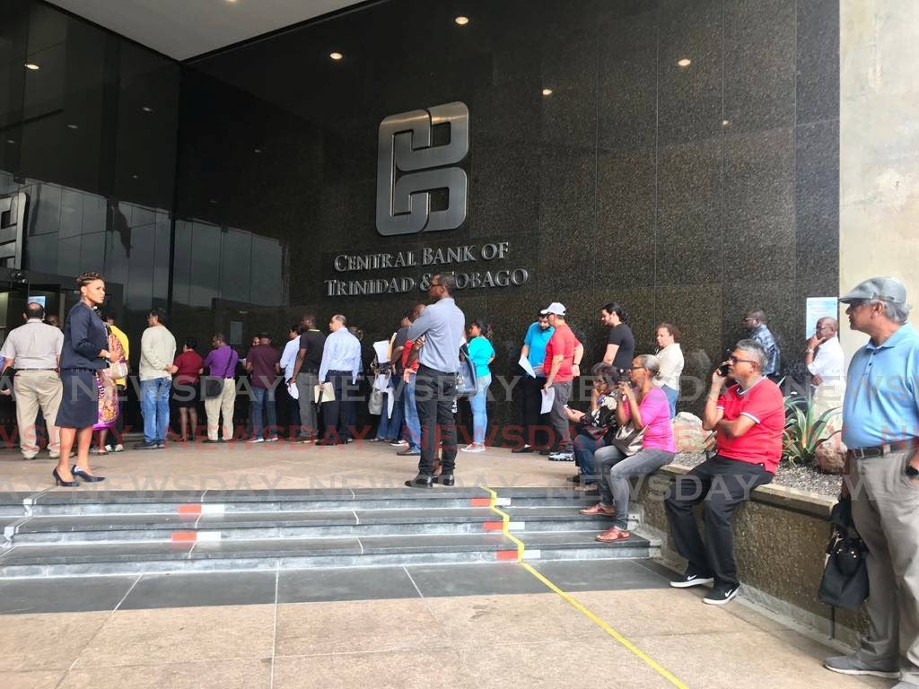 LONG LINE: Citizens in the line to change their old $100 cotton notes to the new polymer notes at the Central Bank, Port of Spain on Wednesday. - Julien Neaves