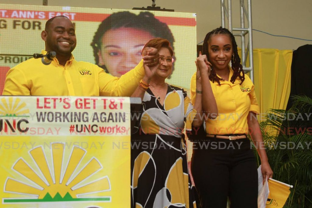 Political leader of the UNC Kamla Persad-Bissessar, centre, presents two candidates for the upcoming general election during a political meeting at the Couva Multi-Purpose Hall on Sunday. Sean Sobers, left, will contest San Fernando West and Kenya Charles will contest St Ann's East. - Marvin Hamilton