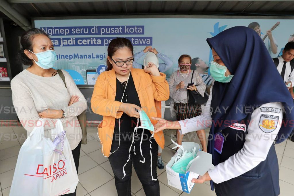 Train officers distribute protective face masks to passengers at a train station in Jakarta, Indonesia on Tuesday. (AP) -