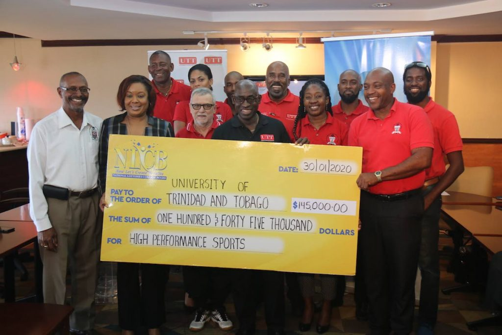 Susan Worrell of NLCB, second from left, presents a cheque to UTT sports officials at the Queen's Park Oval in St Clair, last Thursday. PHOTO COURTESY LESTER KING - LESTER KING