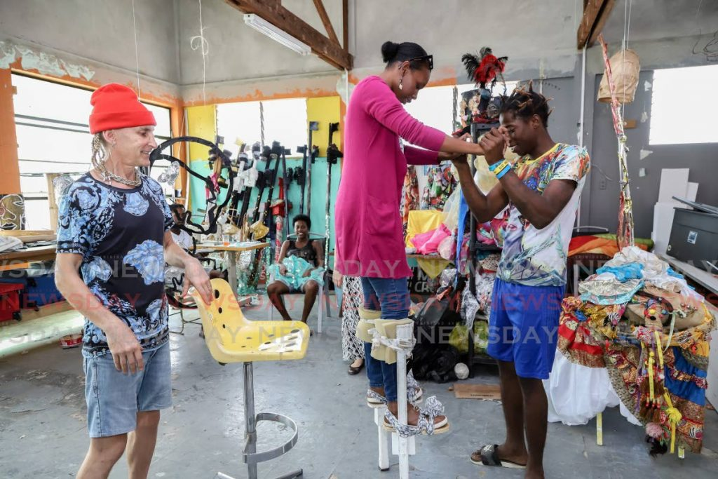 Moko Somokow costume designer Alan Vaughan and band member Russell Grant assists Newsday journalist Kalifa Sarah Clyne to stand and walk on stilts at the band's mas camp in Belmont. - JEFF K MAYERS