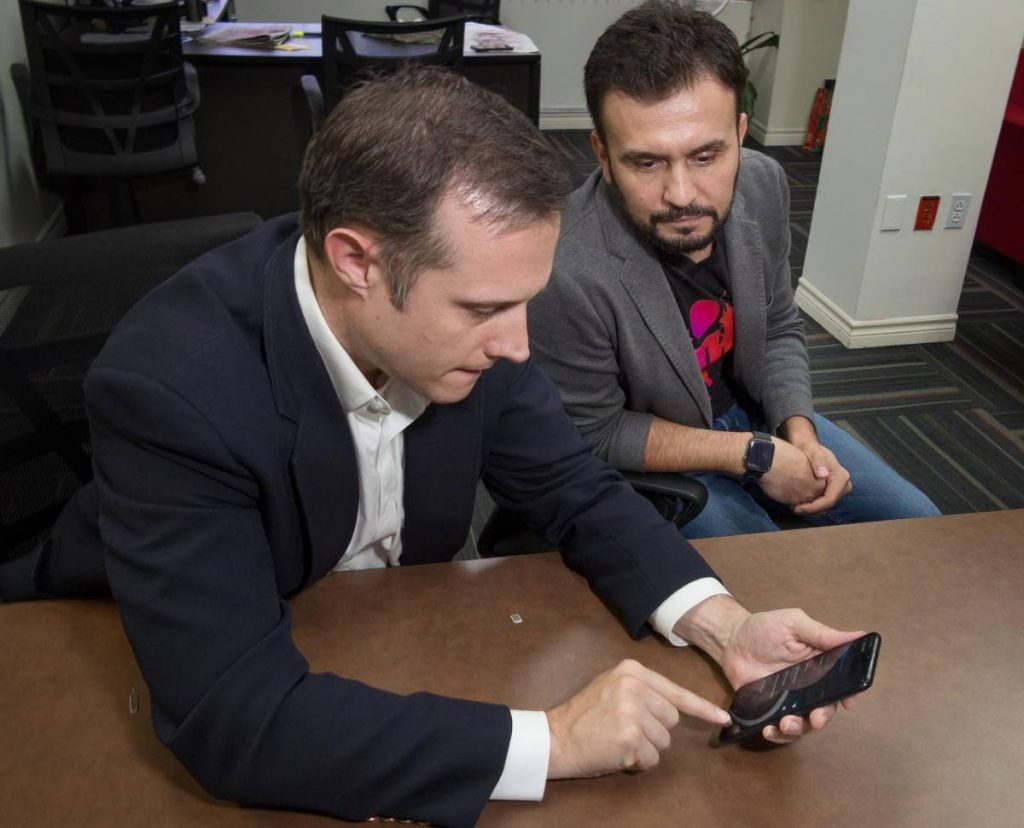 Abraham Smith and Jabbor Kayumov prepare a new smartphone to demonstrate the notification system. Photo by Mark Lyndersay. - Mark Lyndersay