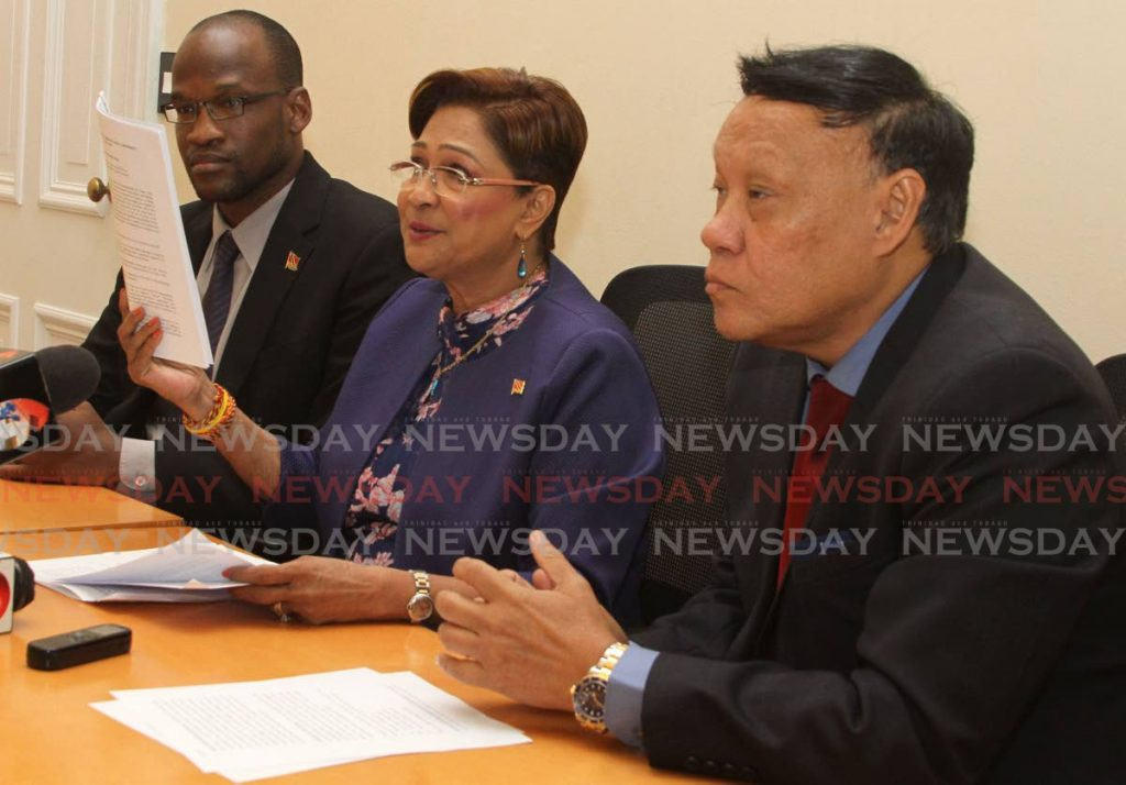 Opposition Leader Kamla Persad-Bissessar is flanked by UNC senator Taharqa Obika and Pointe-a-Pierre MP David Lee at a media conference in the Red House on Friday.  PHOTO BY AYANNA KINSALE - Ayanna Kinsale
