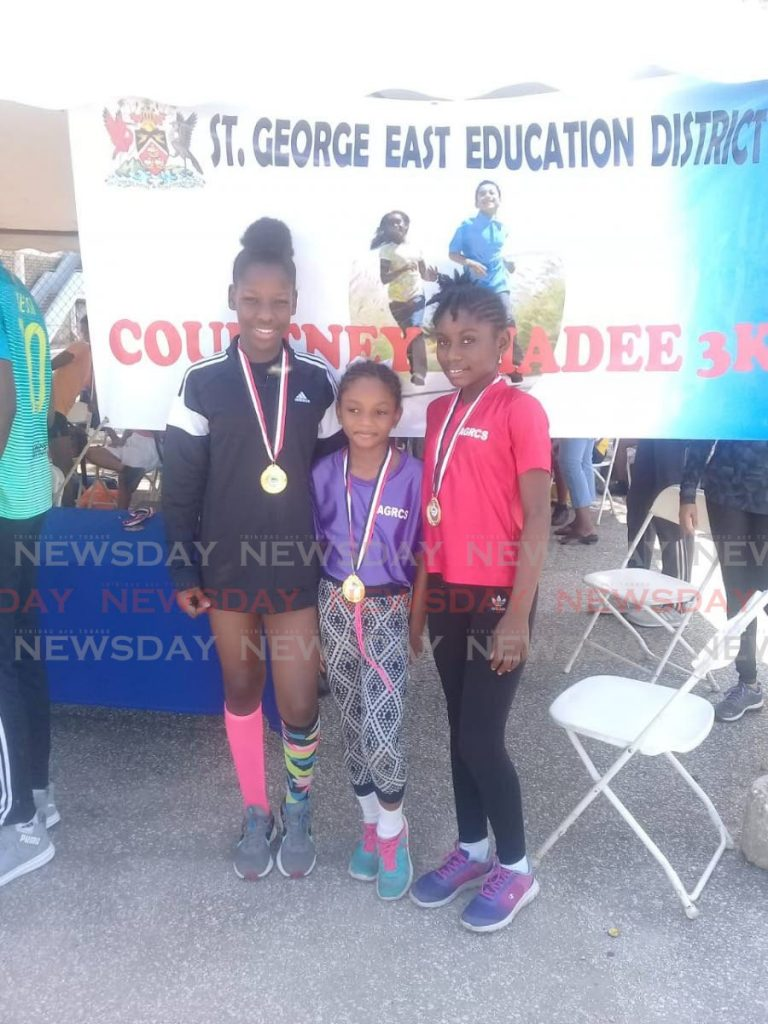 Zariah Pascall (R), of Arima Girls' RC, placed first in the girls category of the St George East Sport Council 3k road race, on Friday, in Arima.  Solissa Mc Carter (L) of D'Abadie Government finished in second place while Pascall's younger sister Zadie was third. -