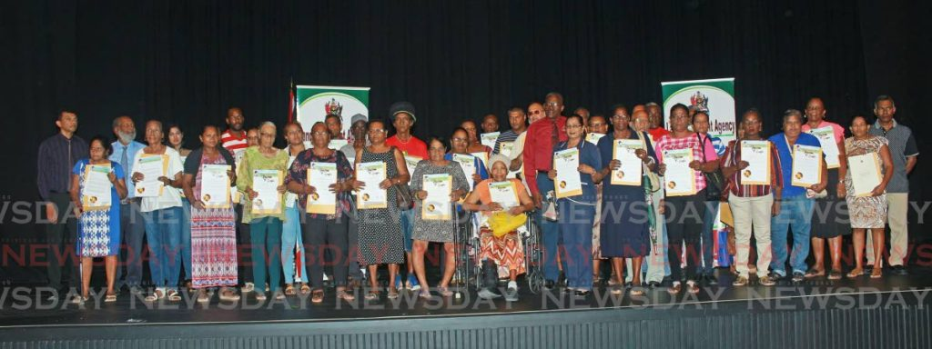 Some of the people who received certificates of comfort pose for a picture with Housing Minister Edmund Dillon at Naparima Bowl, San Fernando on Tuesday. 11-02-2020 PHOTO BY: CHEQUANA WHEELER - CHEQUANA WHEELER