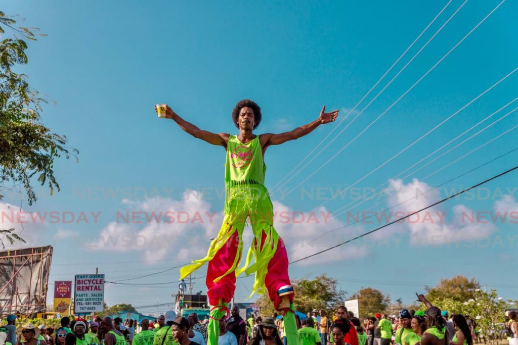 A moko jumbie towers over the revelry at Crown Point J'Ouvert last Carnival.  - DAVID REID