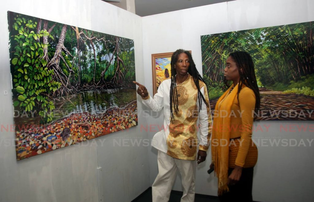 Artist Nerukhi Ato Osei shows one his pieces to Ahavah Charles at his exhibition Re Emergence 2.  - Sureash Cholai