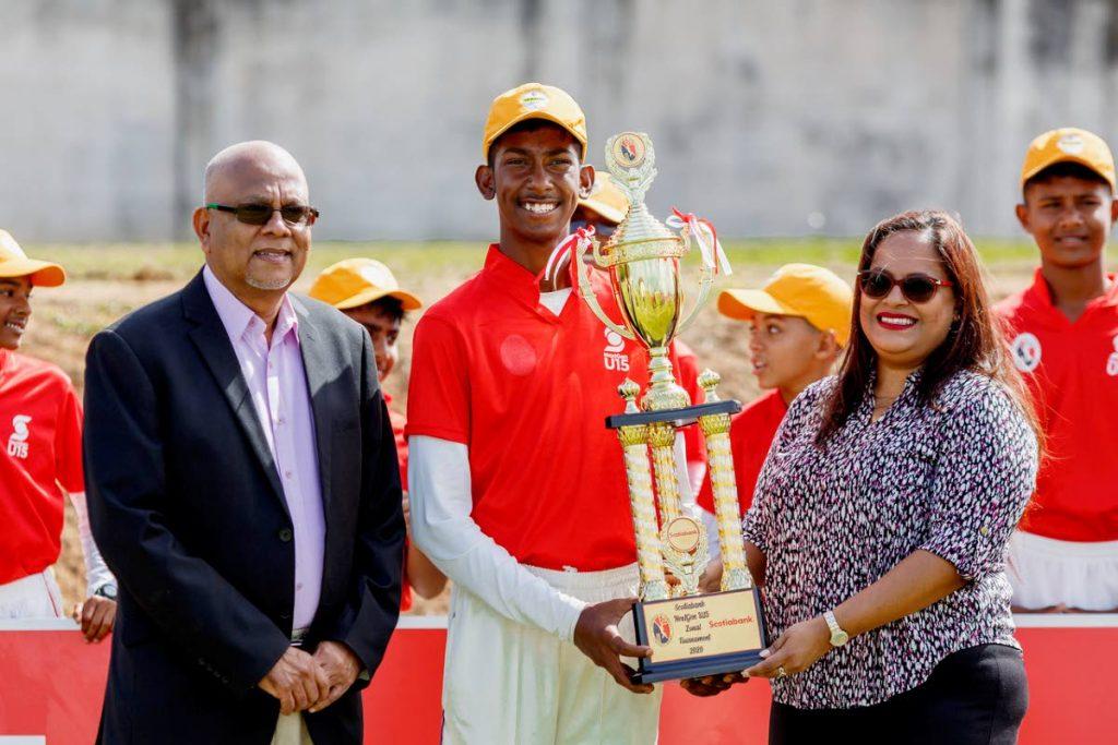 Central Zone captain Luke Ali receives the 2020 NextGen Under-15 Inter Zone trophy from Scotiabank's Cindy Mohammed, on Wednesday. At left is TT Cricket Board president Azim Bassarath.  - courtesy TT Cricket Board