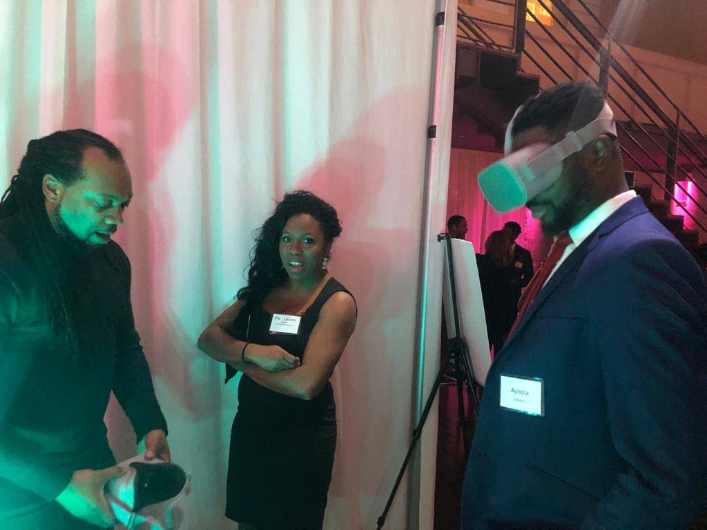 Dwayne Dixon, left,  explains the VR experience to a viewer at the SugaCayne Virtual Reality activation at the Design Exchange in Toronto, Ontario in Canada. PHOTO courtesy  SUGACAYNE DESIGNS  - Paula Lindo