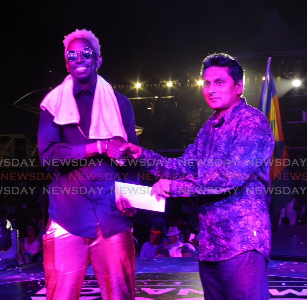 Jesse Stewart, better known as College Boy Jesse, collects his cheque for winning the Groovy category, from Michael Jogee, NLCB Director, at the International Soca Monarch 2020,  Queen's Park Savannah, Port of Spain.  - ROGER JACOB