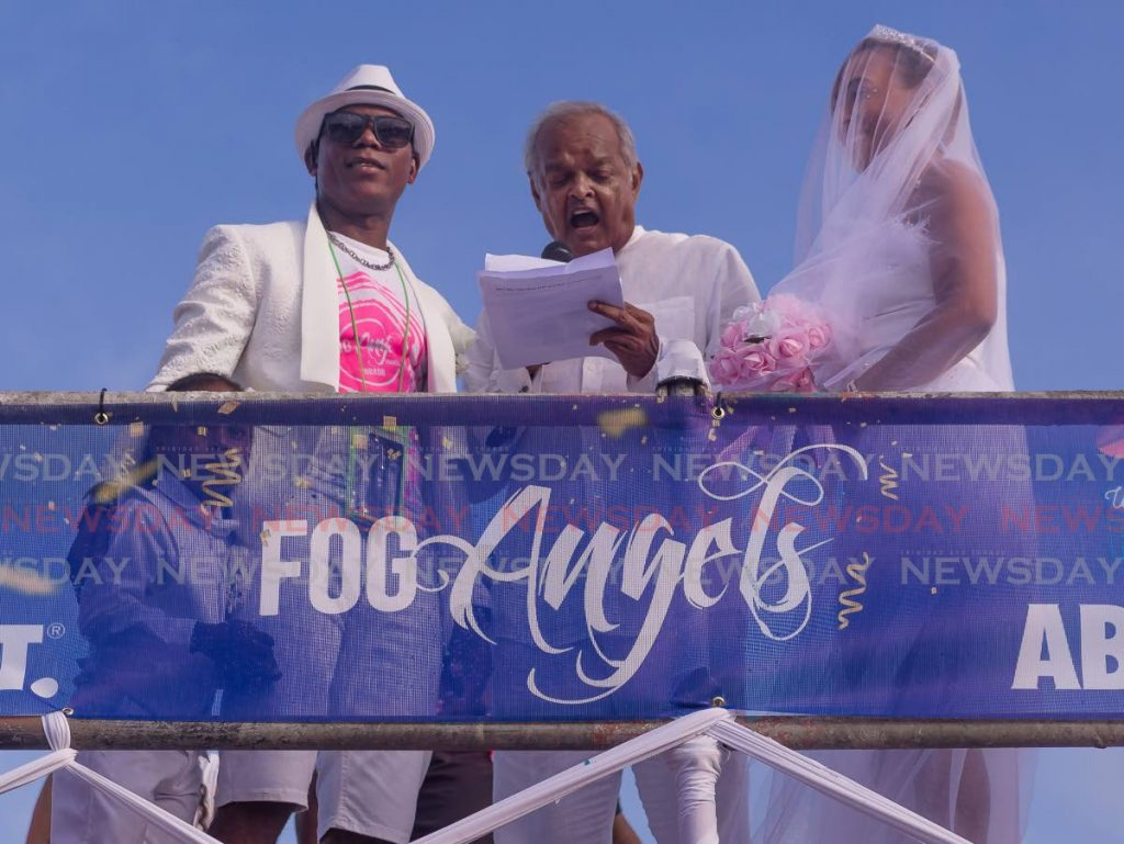 FOG Angels band leader Tele Cruz, left, and Keri Beri, right, held an unofficial wedding ceremony during J'Ouvert celebrations on Monday morning. The pair got married recently but held another ceremony to celebrate their union during Carnival. PHOTO BY DAVID REID -